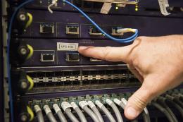 Mão de Operador checando conexões de cabos de rede